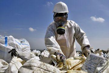 Hombre con equipo anti-toxicidad escarbando entre la basura